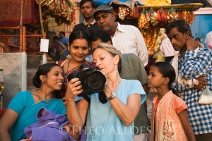 Female tourist/photographer showing digital images to Indian people on Ghats