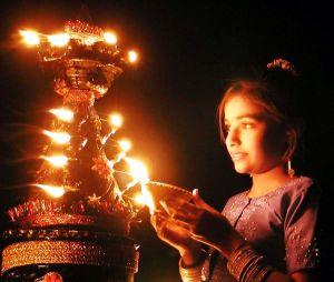 INDIAN GIRL LIGHTS A DEEPAWALI LAMP IN AHMEDABAD