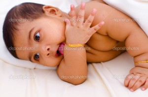 Indian baby girl licking her hand